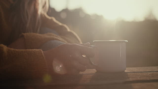 Beautiful woman holding mug with hot coffee at sunrise in the pine forest in the South of France.