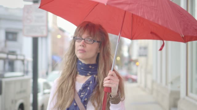 beautiful woman holding red umbrella walks in the rain - 40 44 anni video stock e b–roll