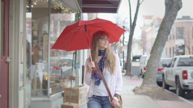 schöne frau mit roten regenschirm geht im regen - schaufenster stock-videos und b-roll-filmmaterial