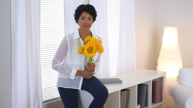 vídeos de stock e filmes b-roll de beautiful woman holding sunflowers by window - fotografia de três quartos
