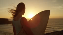 SLOW MOTION CLOSE UP: Beautiful woman holding surfboard gazing at the sunset.