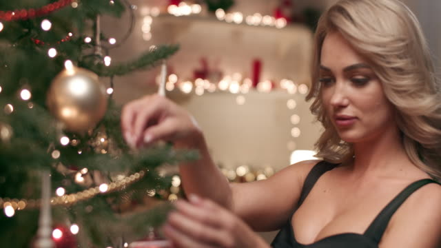 a beautiful woman in a black evening dress, decorating a christmas tree. - blonde hair stock videos & royalty-free footage