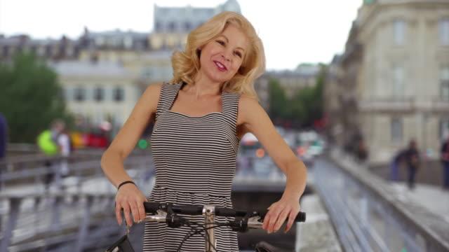 vidéos et rushes de beautiful woman in a dress rides her bike through old streets in paris, france - robe d'été