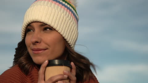 cu beautiful woman in a knit hat drinking coffee - hot drink stock videos & royalty-free footage