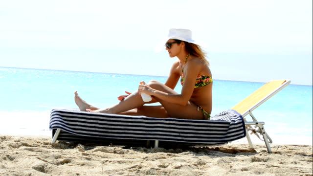 vídeos de stock, filmes e b-roll de mulher bonita em bikini pôr do sol na praia de loção para pele - tomando sol