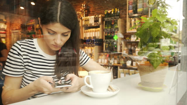 beautiful woman in coffee shop using smart phone. - coffee table stock videos & royalty-free footage