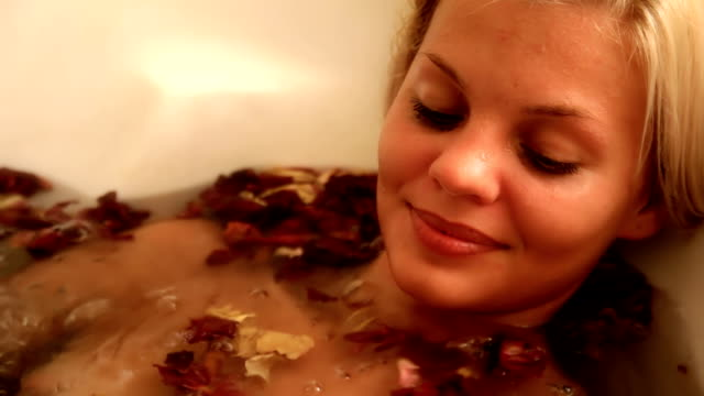 stockvideo's en b-roll-footage met beautiful woman in hot tub with flower petals - bad