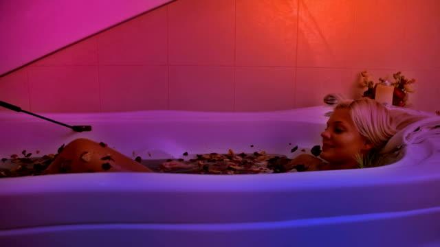 Bella donna con petali di fiori in una vasca idromassaggio