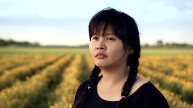 beautiful woman in nature yellow flower scene looking forward