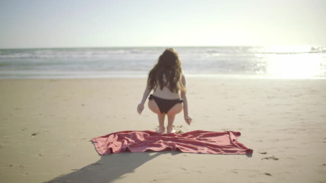 vídeos de stock, filmes e b-roll de beautiful woman in topless on beach in a sunny day - toalha de praia