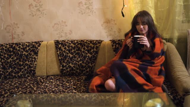 vídeos y material grabado en eventos de stock de beautiful woman in warm cozy plaid drinks tea and looks at you sitting at sofa - tartán