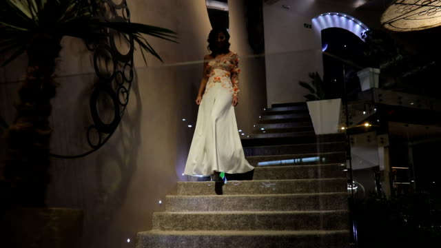 beautiful woman in white dress walking down the steps - indoors stock videos & royalty-free footage