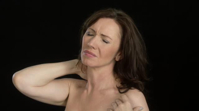 vídeos de stock e filmes b-roll de beautiful woman (45 years old) - intense facial expressions - neck pain - dor no pescoço