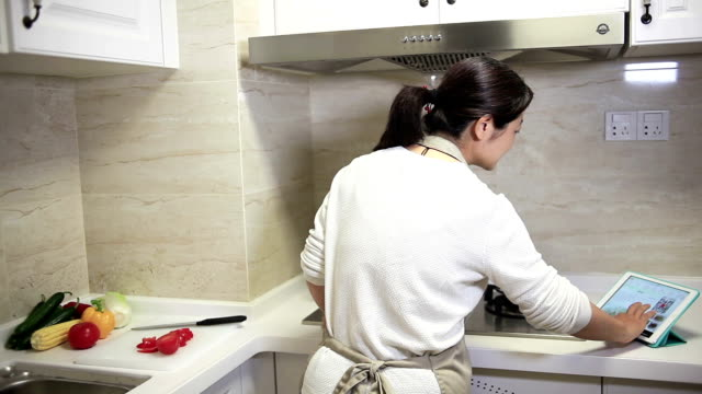 beautiful woman interacting with digital tablet in kitchen - apron stock videos & royalty-free footage
