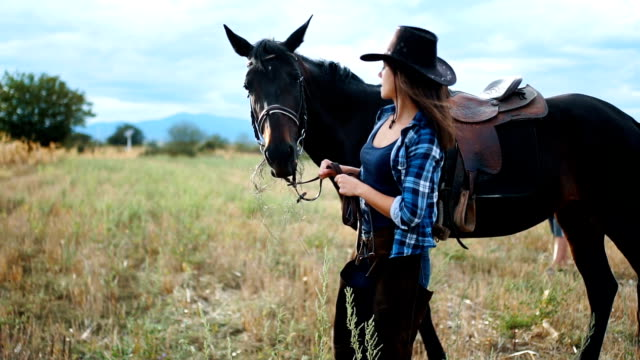 beautiful woman is enjoying nature with her horse - cowgirl stock videos & royalty-free footage