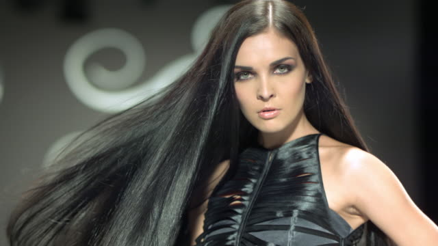 vídeos de stock e filmes b-roll de a beautiful woman is tossing her long beautiful black hair. - cabelo preto