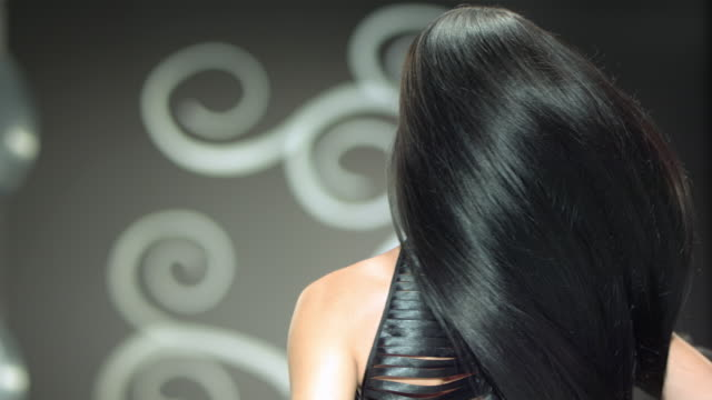 a beautiful woman is tossing her long beautiful black hair. - fashion model stock videos and b-roll footage