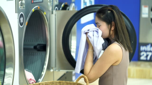 beautiful woman is washing clothes in an automatic laundry shop. - scented stock videos & royalty-free footage