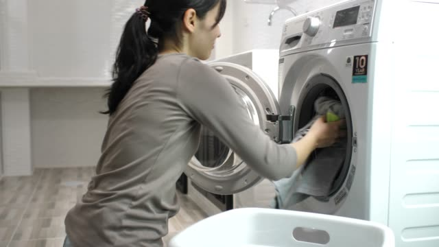 beautiful woman is washing clothes in an automatic laundry - lavori di casa video stock e b–roll