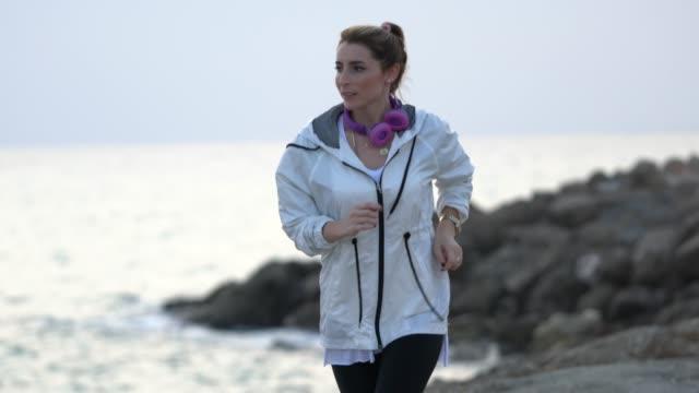 美しい女性のレインコートでジョギング - レインコート点の映像素材/bロール