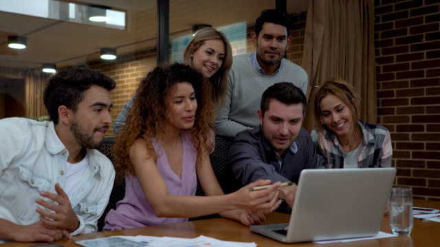 beautiful woman leading a meeting while pointing at the laptop's screen and everyone pitching in - casual clothing stock videos & royalty-free footage