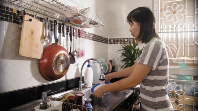 自宅のキッチンでスマート フォン上のポッド キャスト聴いて美しい女性 - 台所点の映像素材/bロール
