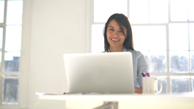 Beautiful woman looking at her laptop while social networking happy