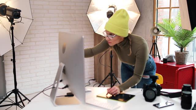 schöne frau schaut sich ihre fotos nach einem fotoshooting an. er schaut sich die fotos an und macht sich notizen. um sie herum sind die kamera und kamera-ausrüstung - digitalkamera bildschirm stock-videos und b-roll-filmmaterial