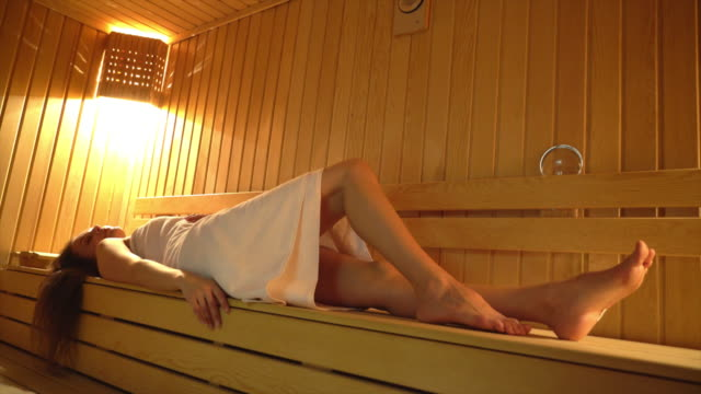 Beautiful woman lying in finnish sauna and relaxation