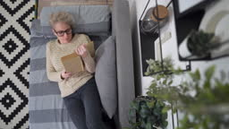 Beautiful woman lying on the bed and reading a book at home