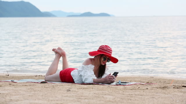 beautiful woman lying on the sand with happiness at the beach relaxing online chat at sunset - one young woman only stock videos & royalty-free footage