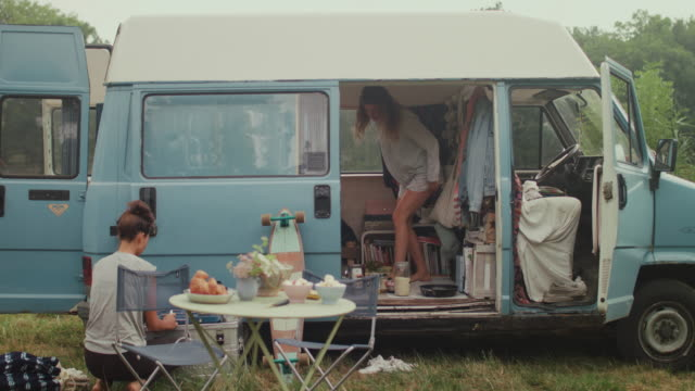 beautiful woman making breakfast in front of a van/camping in the morning - furgone video stock e b–roll