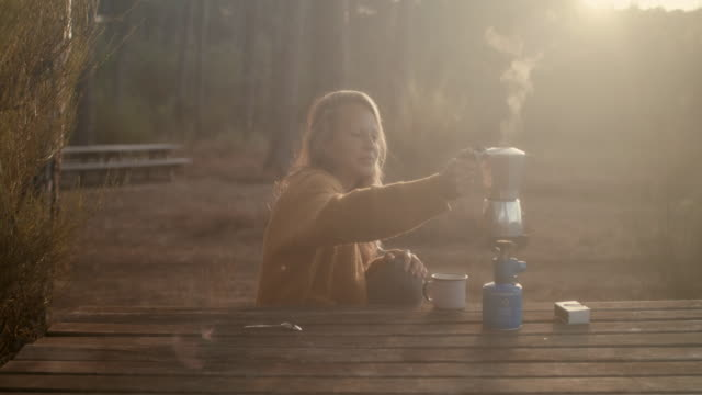 Beautiful woman making coffee at picnic table in the forest with camping stove in the morning at sunrise in the South of France.