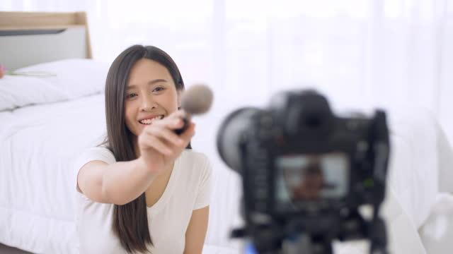 vidéos et rushes de beautiful woman making vlog makeup video, young woman making make-up tutorial - pinceau à blush
