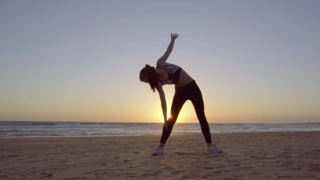 beautiful woman making yoga in the beach at sunset - inarcare la schiena video stock e b–roll