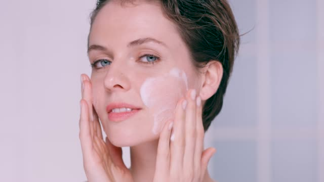 beautiful woman massaging a facial cleanser into her cheeks - washing face stock videos & royalty-free footage