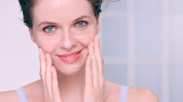 beautiful woman massaging a facial cleanser into her skin - washing face stock videos & royalty-free footage