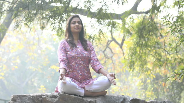 beautiful woman meditating position at park - prayer pose yoga stock videos & royalty-free footage