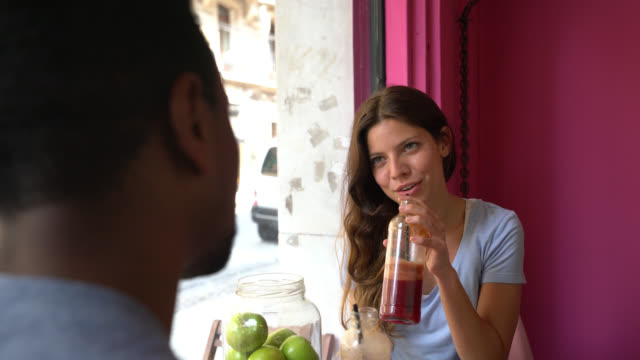 beautiful woman on a date with an unrecognizable black man enjoying a juice and talking - juice drink stock videos and b-roll footage