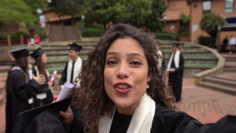 vacker kvinna på en live video chatt upphetsad och glad talar om hennes prestation efter examensceremoni - examen bildbanksvideor och videomaterial från bakom kulisserna