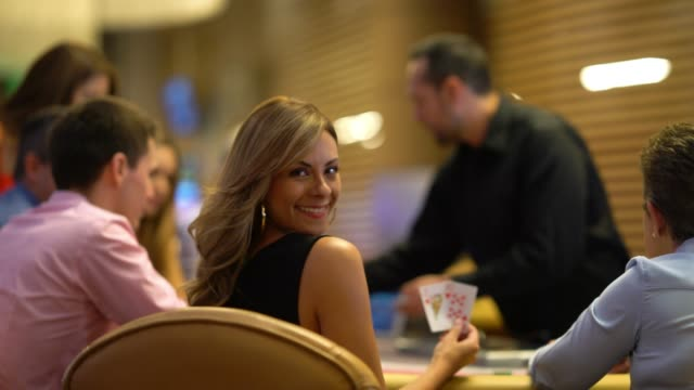 beautiful woman on a lucky strike at the casino playing blackjack looking at camera smiling - blackjack stock videos and b-roll footage