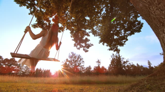 slo mo beautiful woman on a swing in sunset - dress stock videos and b-roll footage