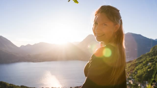 Beautiful woman on holidays, standing at a viewpoint above lake