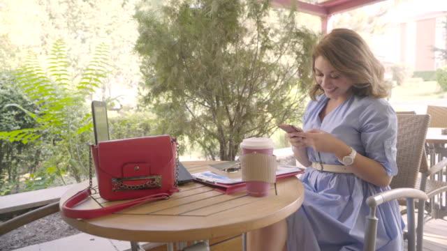 vidéos et rushes de belle femme en ligne messagerie sur téléphone intelligent - engagement des clients