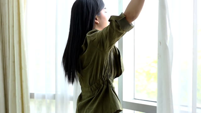 Beautiful woman opens curtains in the house.