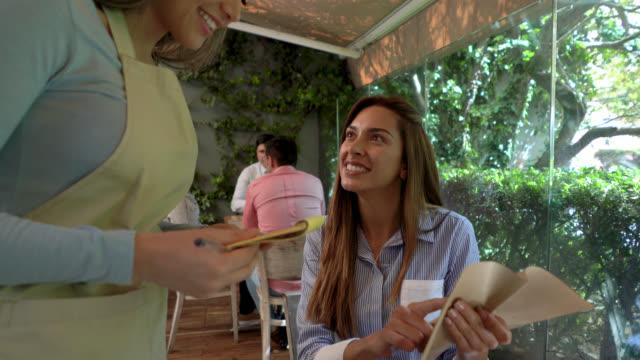 vídeos y material grabado en eventos de stock de hermosa mujer ordenar algo en el menú y la camarera toma su orden - delantal