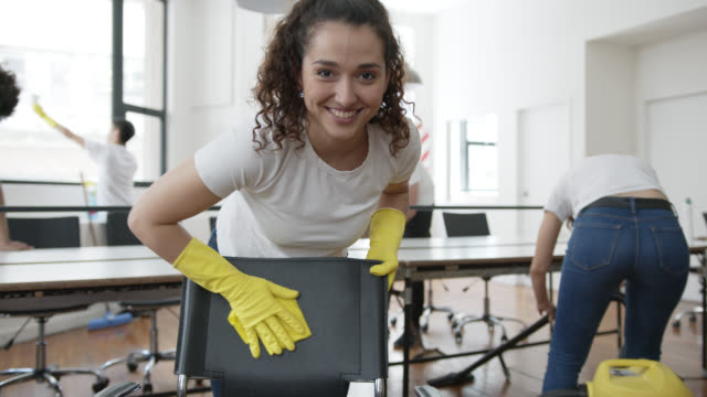 beautiful woman part of a team cleaning team at an office cleaning a chair and then smiling at camera - crew stock videos & royalty-free footage