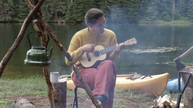 beautiful woman playing on ukulele in nature, camping in nature, enjoyment next to the campfire outdoor. - boho stock videos & royalty-free footage