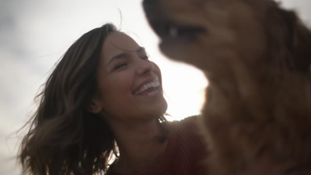 cu beautiful woman playing with her dog outdoors. - piacere video stock e b–roll