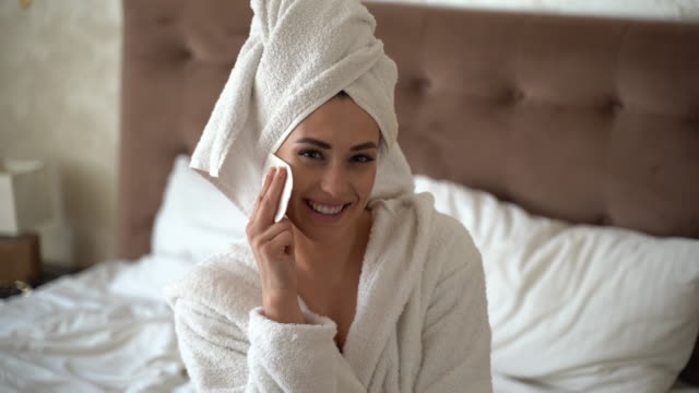 beautiful woman portrait cleansing her face with a cotton bud - bathrobe stock videos & royalty-free footage